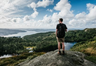 man admiring lake view from top of mountain
