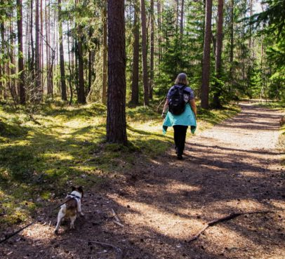 woman walking on a trail with dog