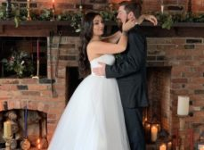 bride and groom in front of a fireplace
