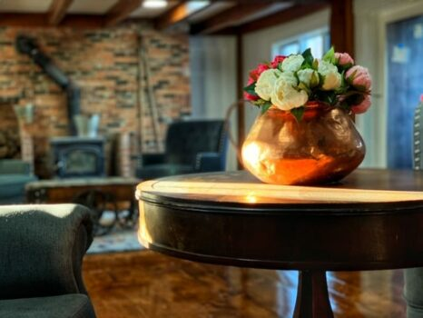 flower on a copper pot on top of a table