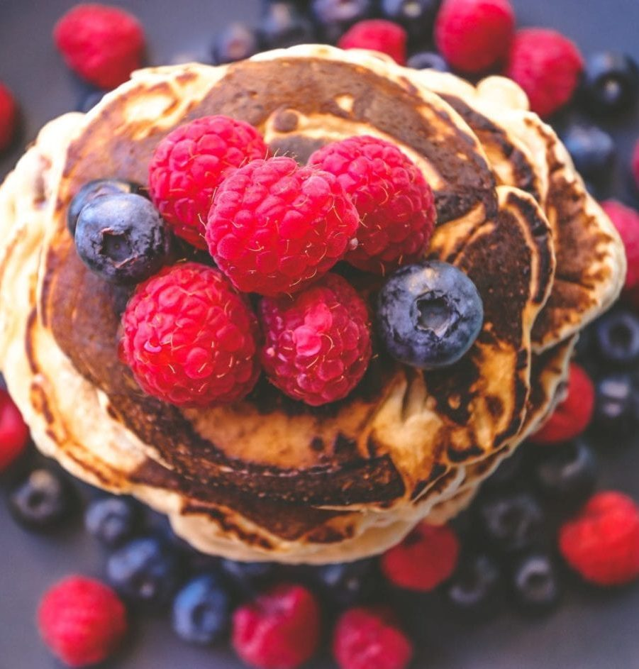 a stack of homemade pancakes topped with fresh raspberries and blueberries