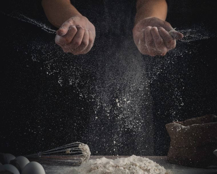 hands dusting flour while baking