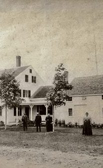 historic picture of the farmhouse with people posing in front