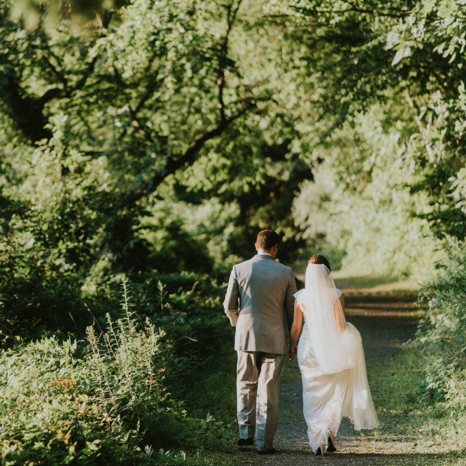 newly wed couple walking down a lush green path hand-in-hand